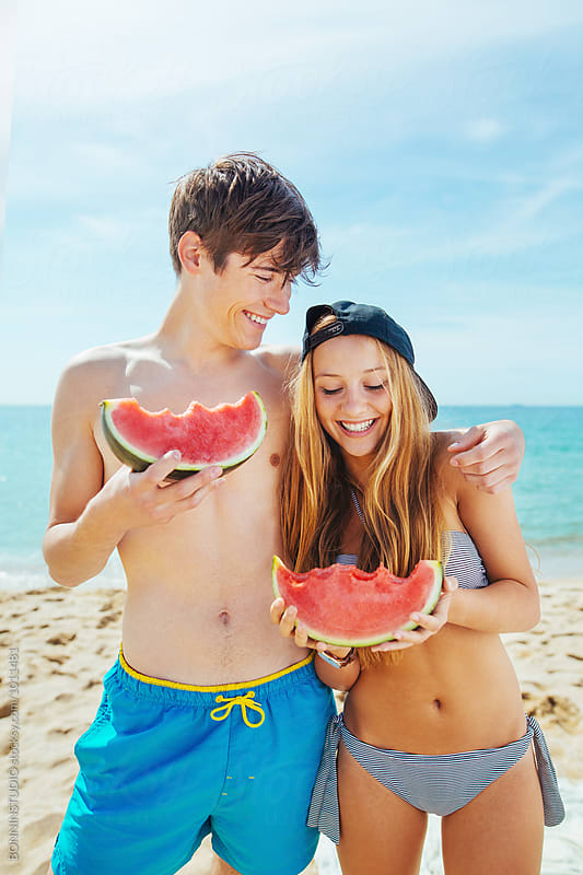 Portrait of a smiling teenage couple eating a watermelon on the beach. by BONNINSTUDIO for Stocksy United