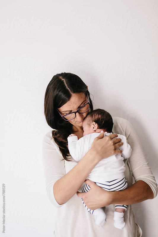 Mother holding her little daughter in her arms in front of white wall by Peter Meciar for Stocksy United