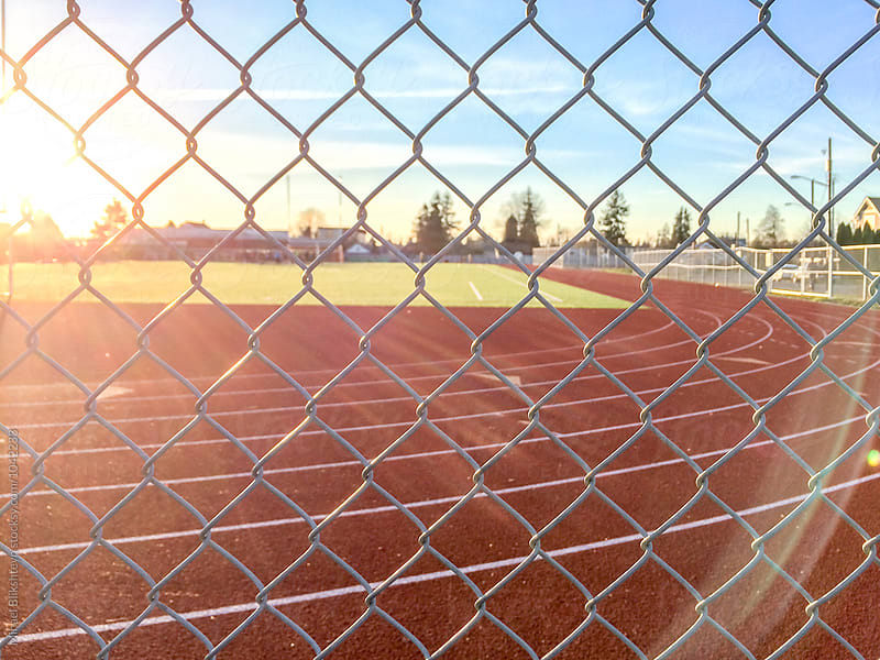 Athletic running track seen through chainlink fence at sunset by Mihael Blikshteyn for Stocksy United