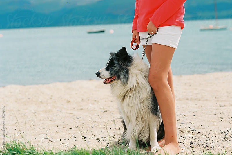 young woman holding a dog by the sea