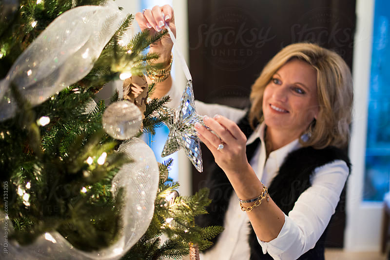 Attractive Woman Hanging Christmas Decorations on Christmas Tree by JP Danko for Stocksy United