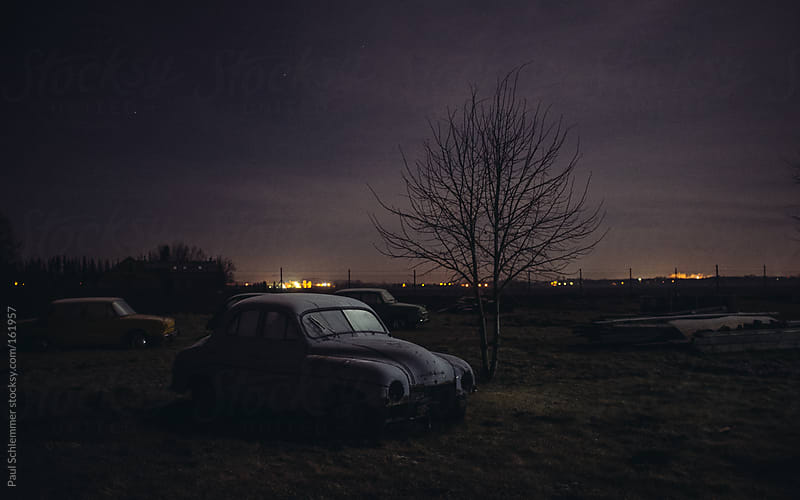 old car wreck at night by Paul Schlemmer for Stocksy United