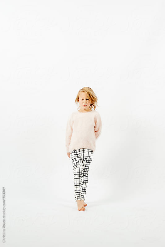 Young girl stands against white studio background by Christina Rouse for Stocksy United