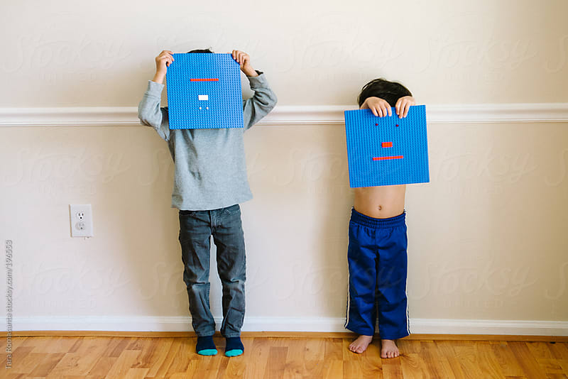 two little boys hide behind blue building block toy emoticon faces by Tara Romasanta for Stocksy United
