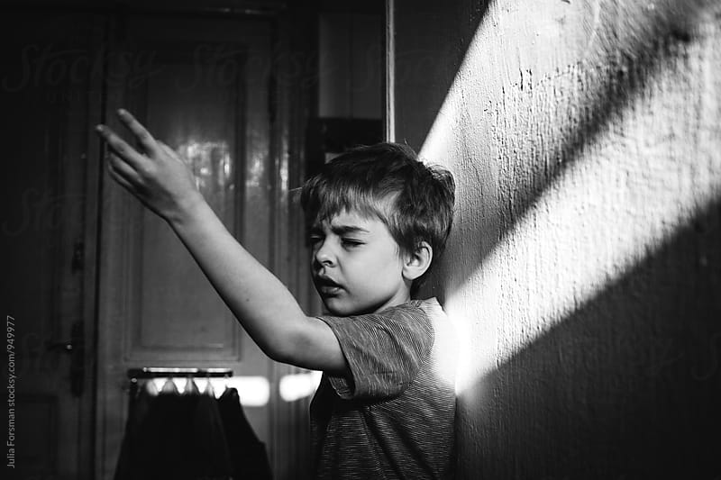 Child explains something waving his arms and closing his eyes. by Julia Forsman for Stocksy United