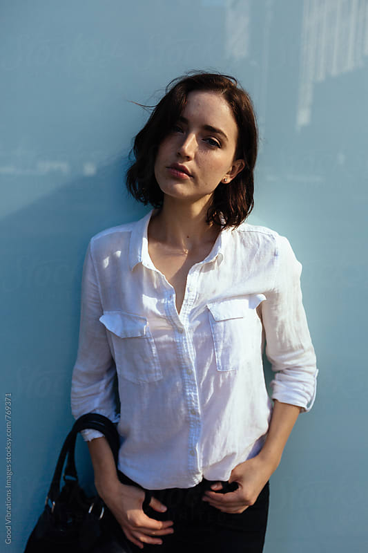 Brunette portrait against a blue glass wall by Good Vibrations Images for Stocksy United