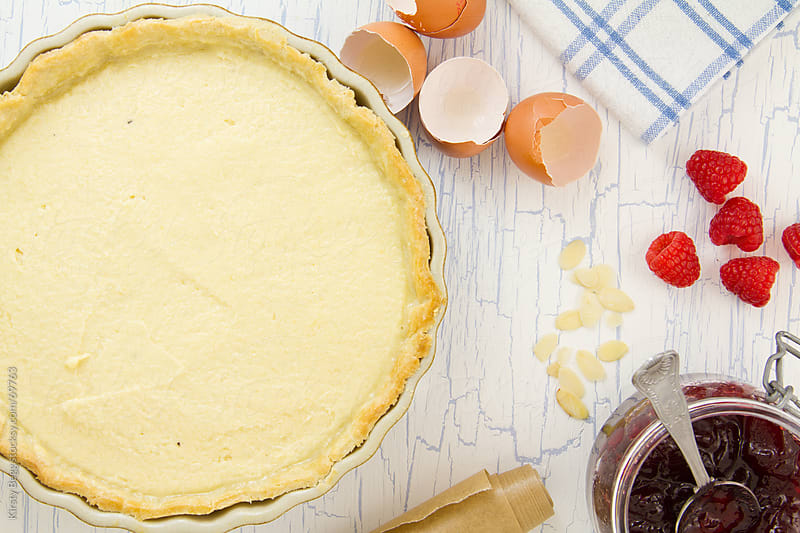 Unbaked Bakewell Tart with baking ingredients around by Kirsty Begg for Stocksy United