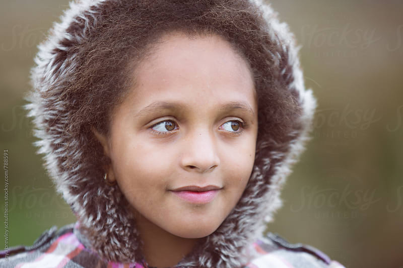 Closeup portrait of a beautiful young girl with shaggy winter hoody smiling sweetly by anya brewley schultheiss for Stocksy United