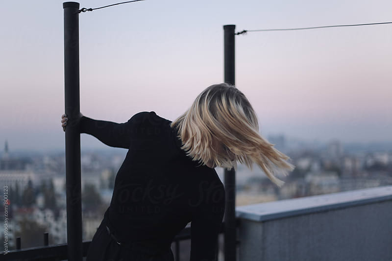Blonde woman on the roof of the building during sunset  by VeaVea for Stocksy United