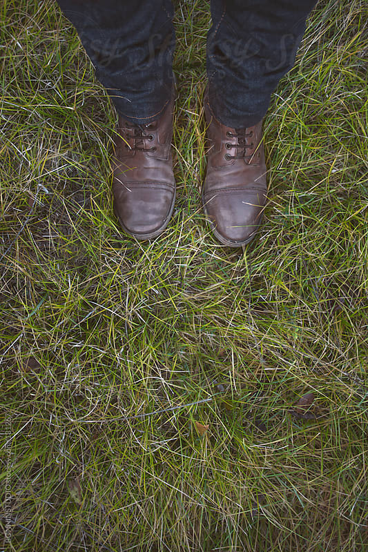 Man standing on green grass. by BONNINSTUDIO for Stocksy United