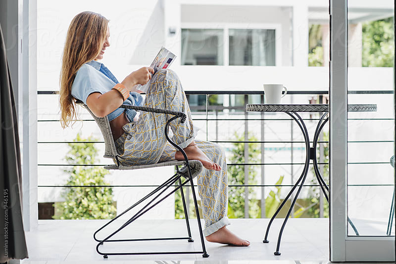 Woman Reading a Magazine on the Balcony at Home by Lumina for Stocksy United