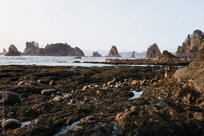 young man explores northwest beach by Jesse Morrow for Stocksy United