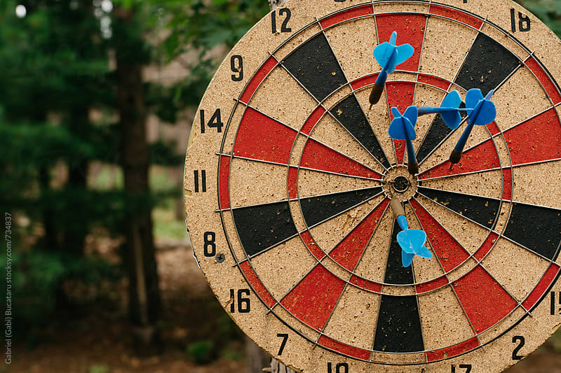 Darts in a dartboard outdoors by Gabriel (Gabi) Bucataru for Stocksy United