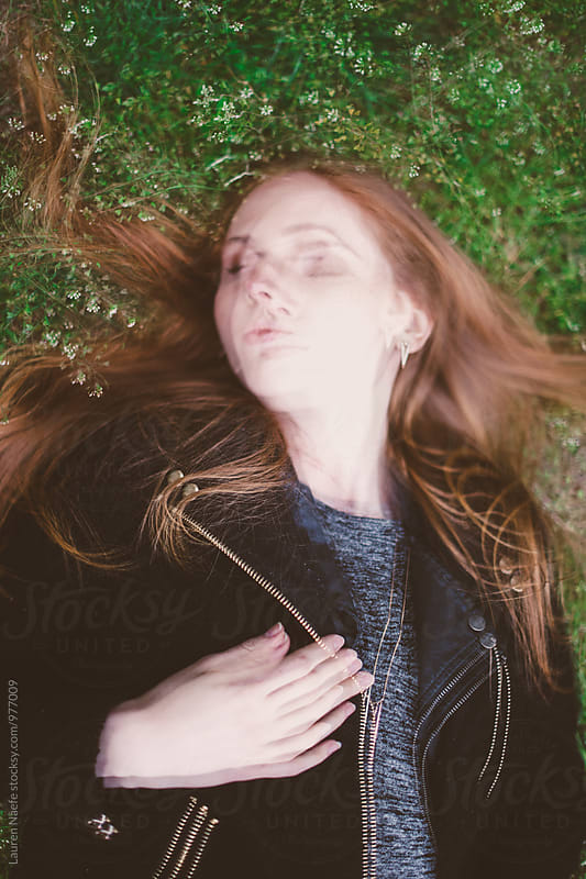 Blurred portrait of young woman lying in the grass by Lauren Naefe for Stocksy United