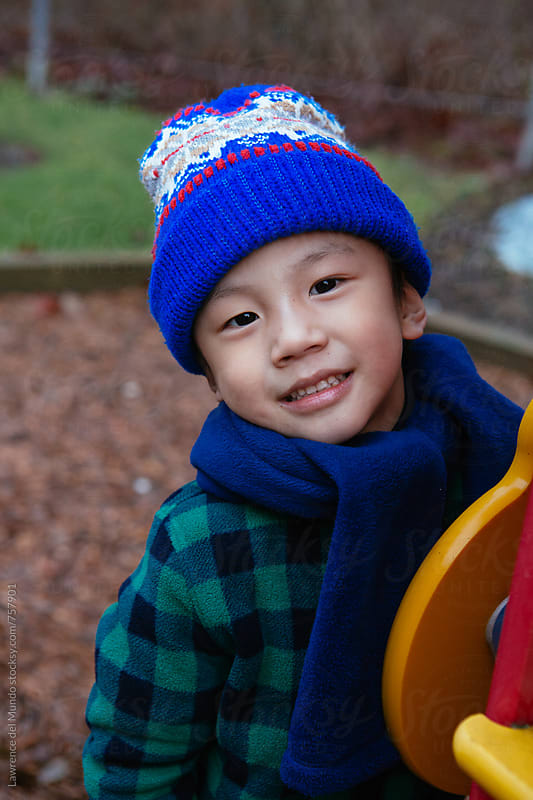 Portrait of a cute, adorable, smiling young kid wearing cold weather clothes at the park. by Lawrence del Mundo for Stocksy United