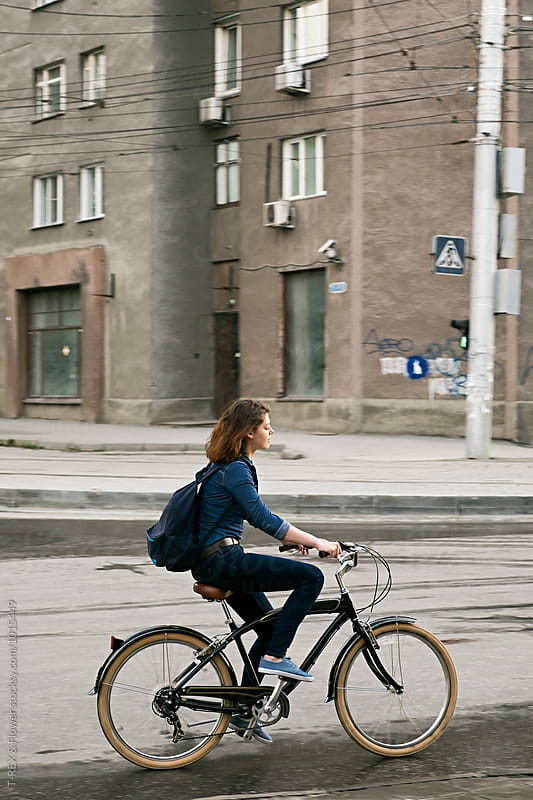Side view of brunette riding bike along road by Danil Nevsky for Stocksy United