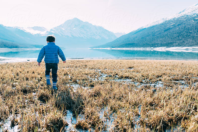 little boy walking toward lake surrounded by mountains by Tara Romasanta for Stocksy United