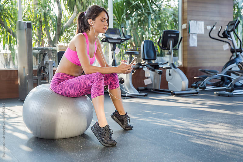 Woman sitting at a pilates ball - listening to music after a successful workout