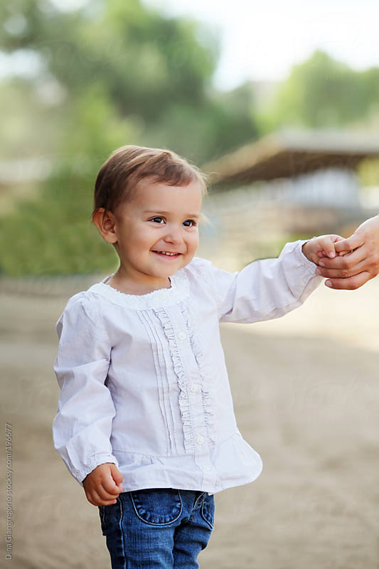 Brunette toddler holding daddy's hand and smiling by Dina Giangregorio for Stocksy United