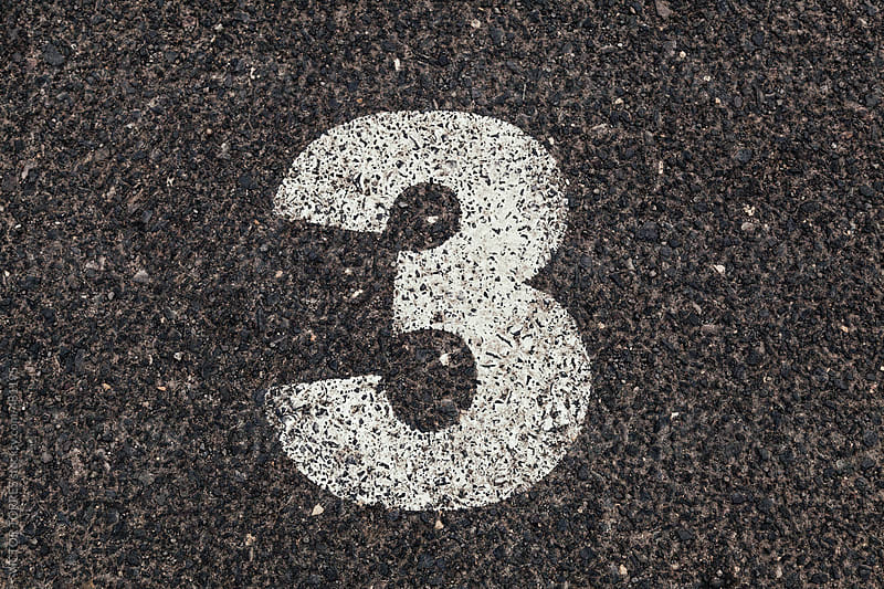 Number 3 Printed on White Over Dirty Asphalt by VICTOR TORRES for Stocksy United