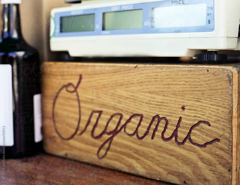 Wood sign saying organic near a scale by Carolyn Lagattuta for Stocksy United