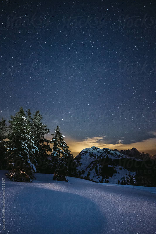 snowcovered austrian mountain landscape under starry night by Leander Nardin for Stocksy United