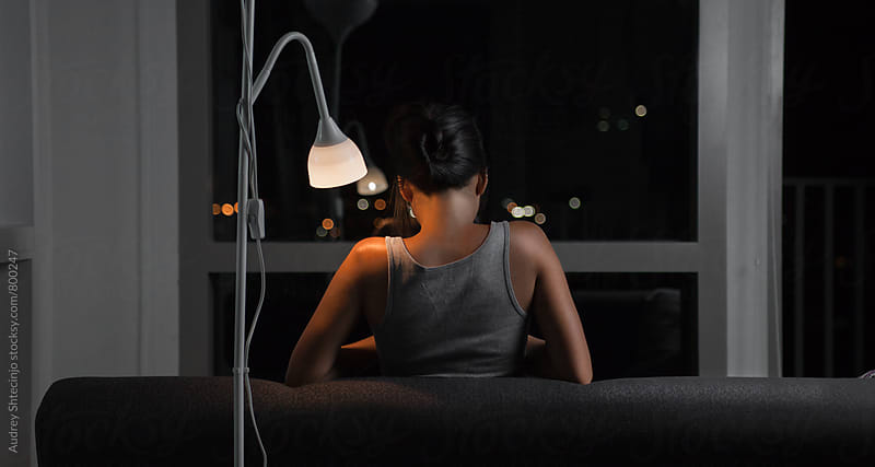 Evening scene of young woman sitting on sofa/look from behind. by Marko Milanovic for Stocksy United