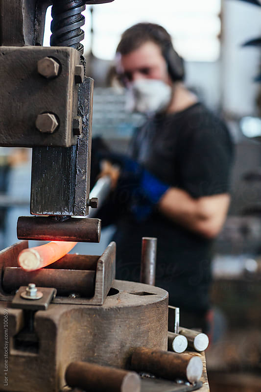 Young man working hot steel on a fly press by Lior + Lone for Stocksy United