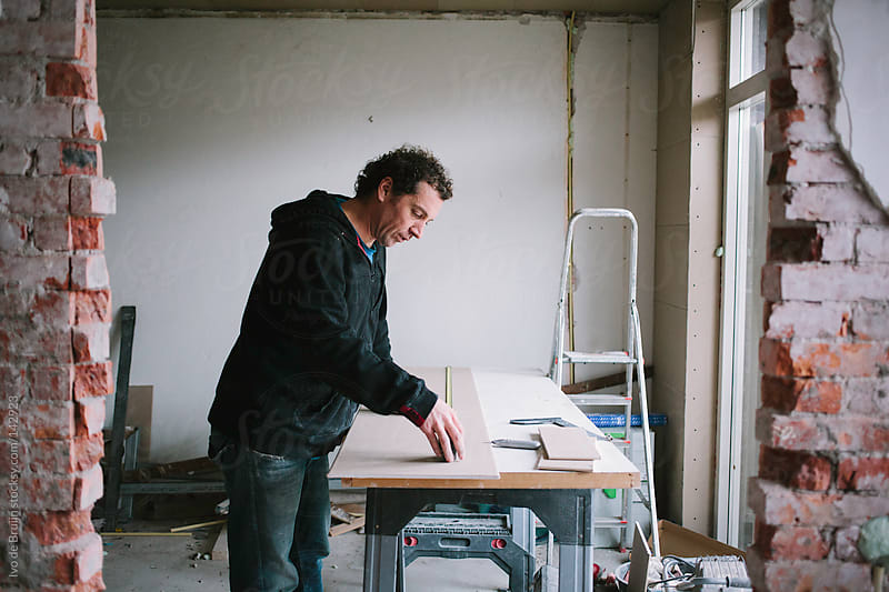 A man accurately measuring plasterboard while working on his workbench at home by Ivo de Bruijn for Stocksy United