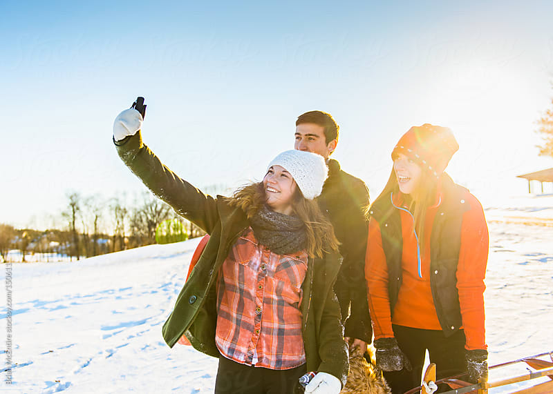 Friends take selfie on sledding hill by Brian McEntire for Stocksy United