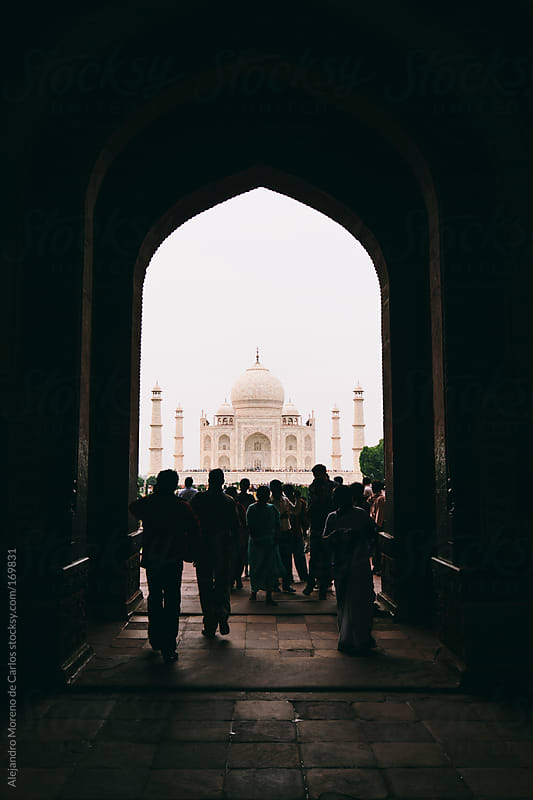 Taj Mahal palace seen through a door in shadow with people silhouette, Agra, India travel image by Alejandro Moreno de Carlos for Stocksy United