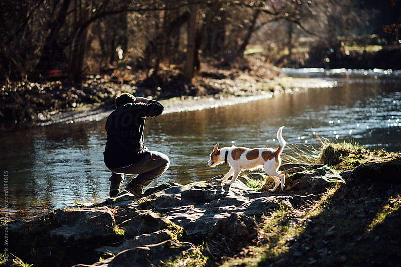 Man with dog taking a photograph by the river bank by Boris Jovanovic for Stocksy United