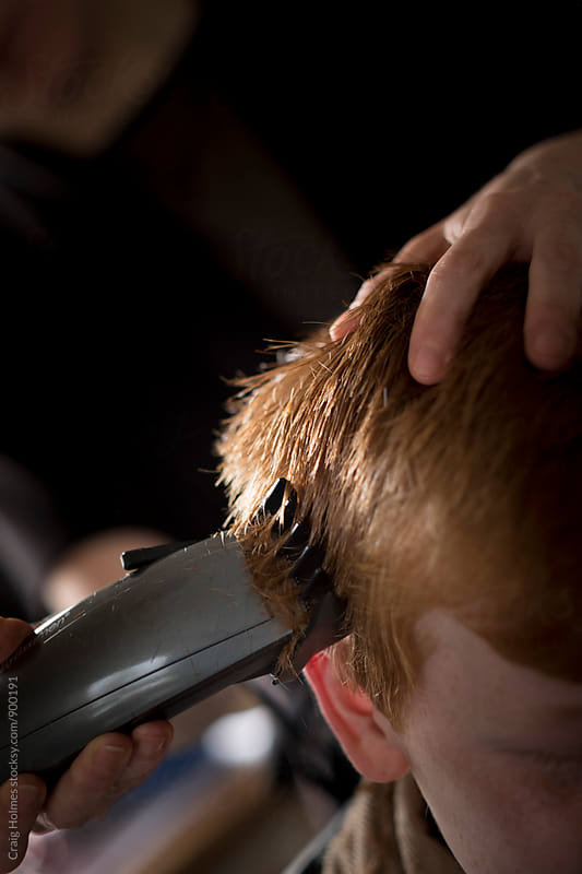 A boy having his hair cut with clippers and scissors. by Craig Holmes for Stocksy United