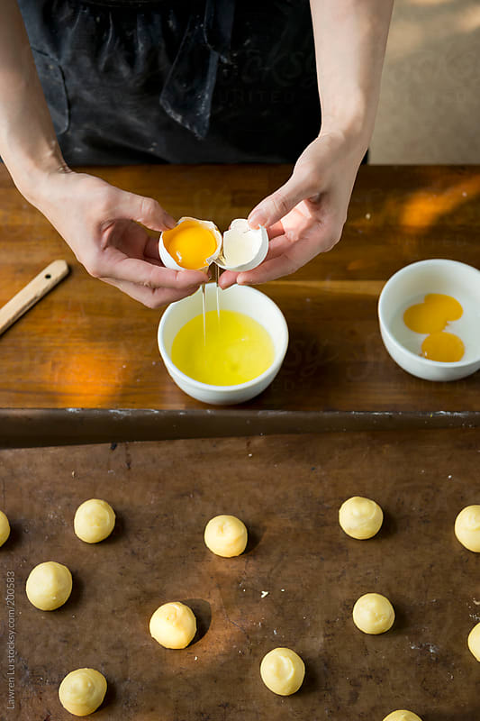 Woman hands separating egg yolk for brushing bread by Lawren Lu for Stocksy United