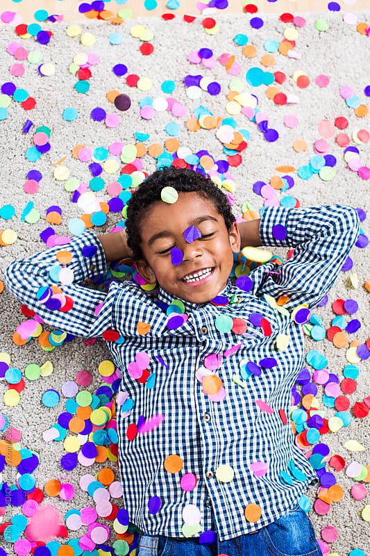 Little boy playing as confetti falls from above. by BONNINSTUDIO for Stocksy United