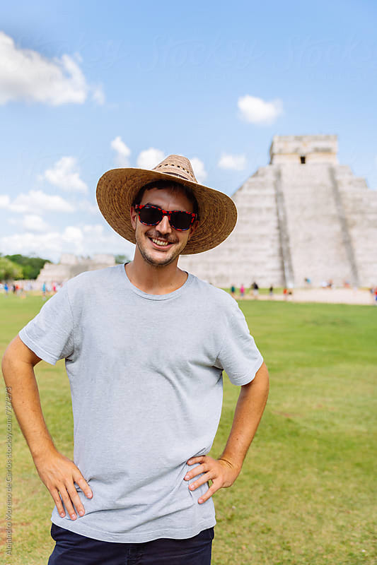 Young smiling tourist man in front of Kukulkan pyramid in Chichen Itza, Mexico by Alejandro Moreno de Carlos for Stocksy United
