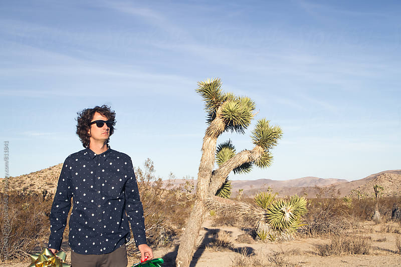 Man Holding Oversized Gift Bows with Joshua Tree by MEGHAN PINSONNEAULT for Stocksy United