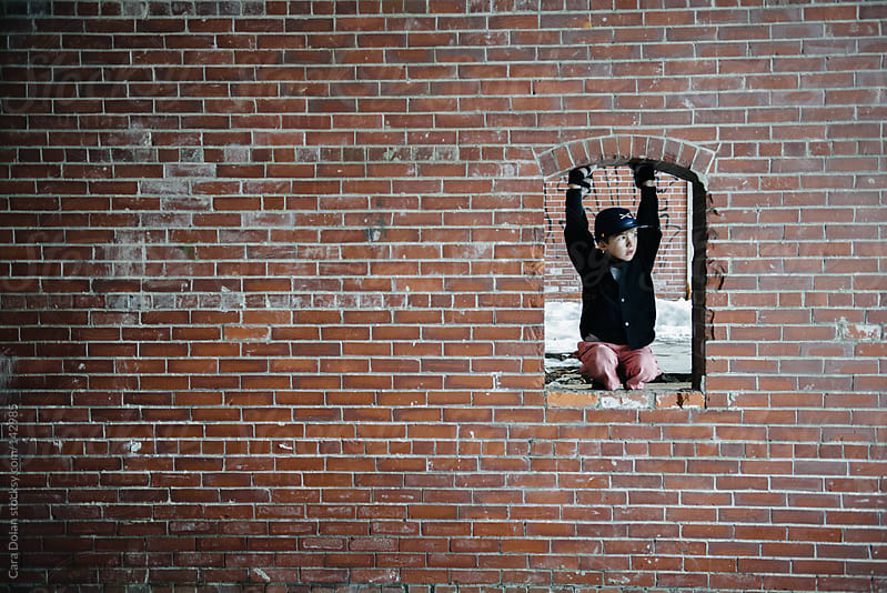 Boy sits in open window of abandoned building by Cara Dolan for Stocksy United