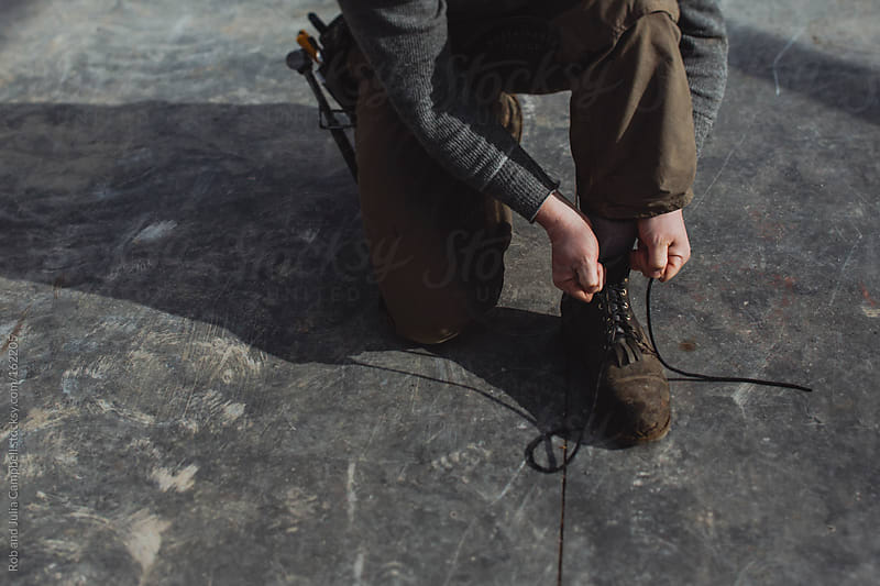 Carpenter man tying laces of work boots at construction site by Rob and Julia Campbell for Stocksy United