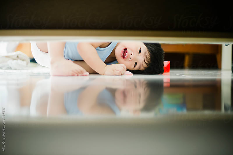 Baby peeking under a sofa by Alita Ong for Stocksy United