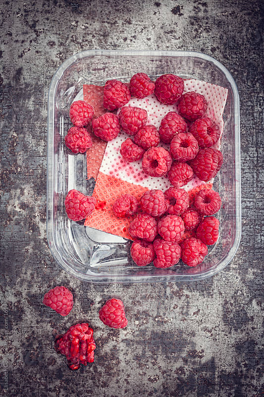 Raspberries in plastic container on old metal baking tray by Elisabeth Coelfen for Stocksy United