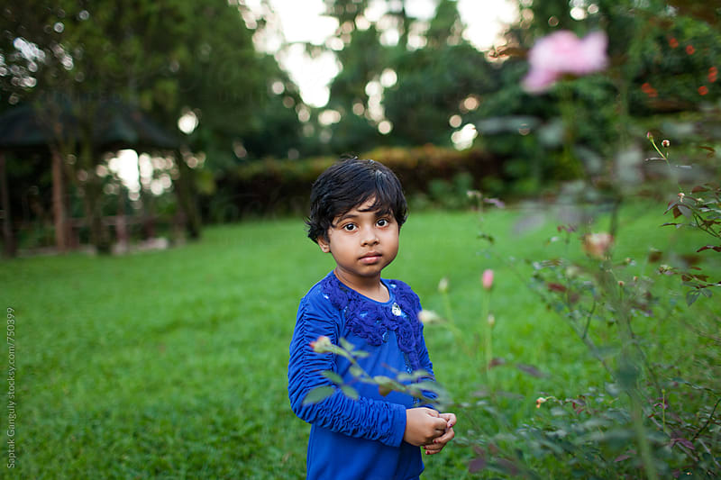 Child with a blank expression looking at camera in the lawn by Saptak Ganguly for Stocksy United