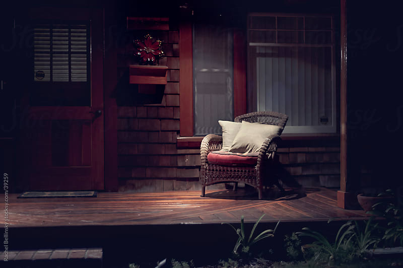A cozy chair on a dark wooden deck at night by Rachel Bellinsky for Stocksy United