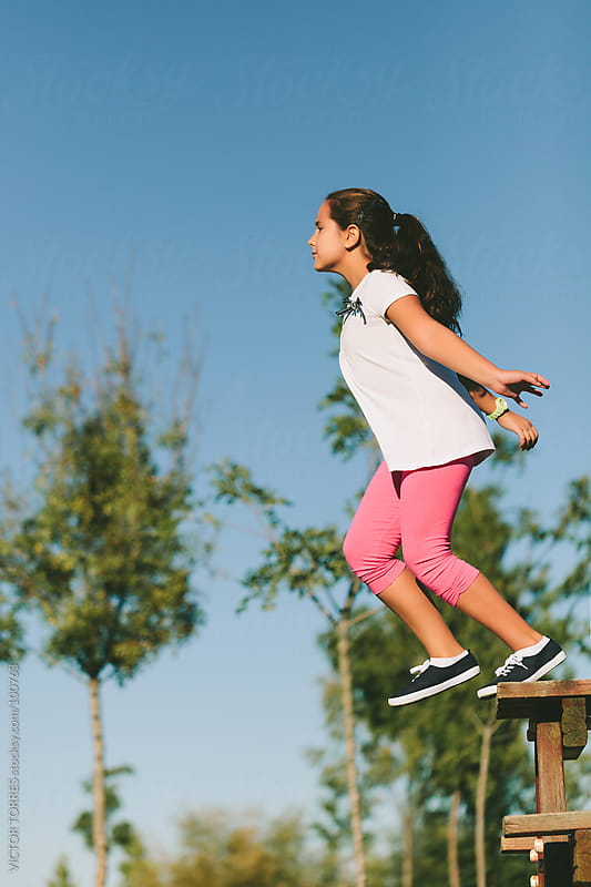 Little Girl Jumping From a Wooden Table by VICTOR TORRES for Stocksy United