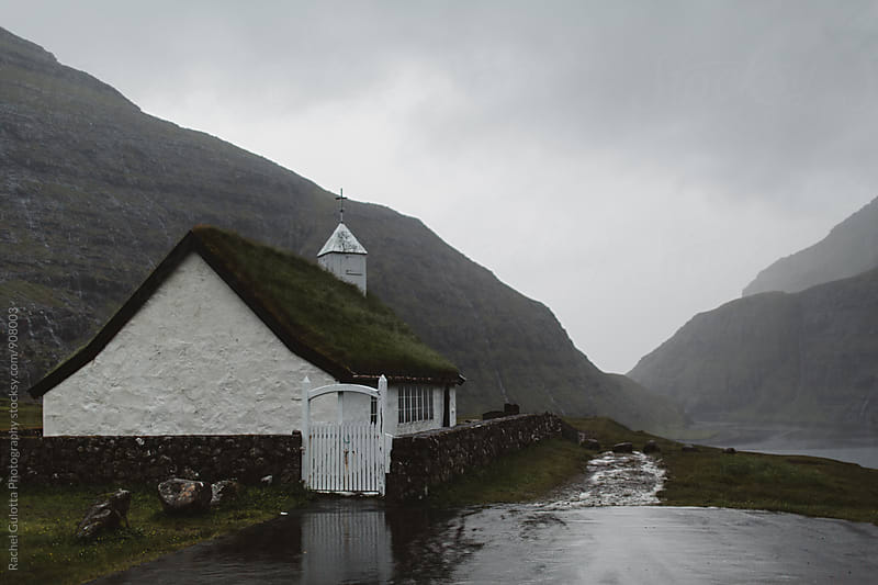 A Grass Roof Church at Saksun, Faroe Islands in the Mountains next to the Atlantic Ocean by Rachel Gulotta Photography for Stocksy United