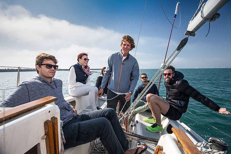 Group of smiling friends sailing on yacht ready for ocean sailboat  adventure by Jonathan Caramanus for Stocksy United