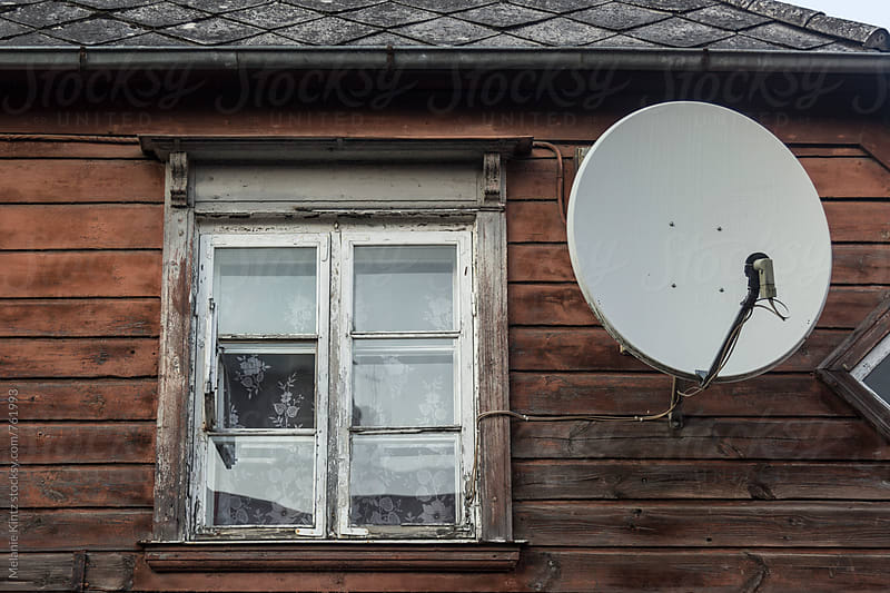 Traditional wooden house in decay with modern satellite dish by Melanie Kintz for Stocksy United