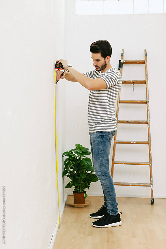 Young man measuring the wall with tape measure .  by BONNINSTUDIO for Stocksy United