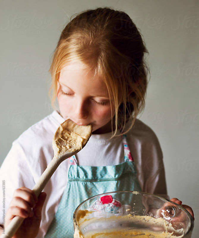 A little girl licking cake mixture off a spoon. by Helen Rushbrook for Stocksy United