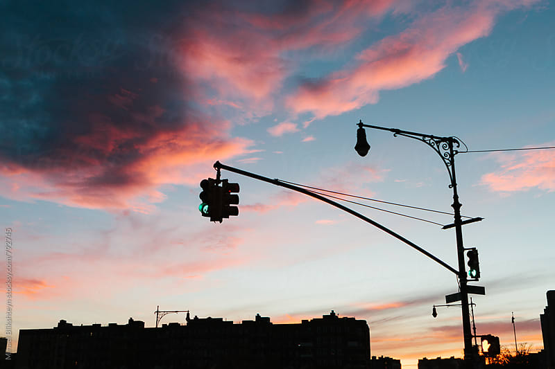 Evening skyline of buildings and traffic light in a city with fiery sunset by Mihael Blikshteyn for Stocksy United